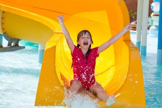 Egy kislány lecsúszik egy vízi csúszdán.
