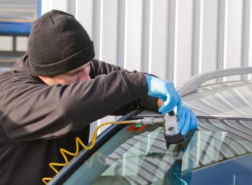 Egy szerelő az autó szélvédőjét javítja.