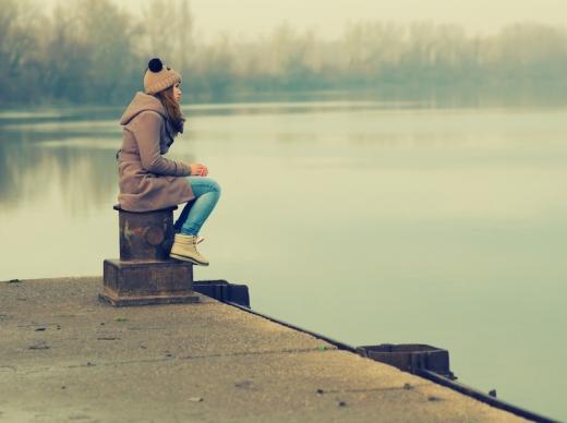 Egy nő ősszel a móló szélén ül.