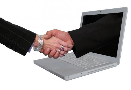 Egy férfi kéz kinyúl egy laptopból és kezet fog egy női kézzel.