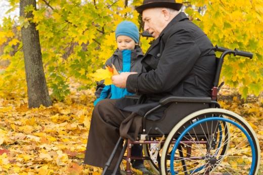 Egy bácsi tolószékben ül, egy kisfiú ül mellette ősszel