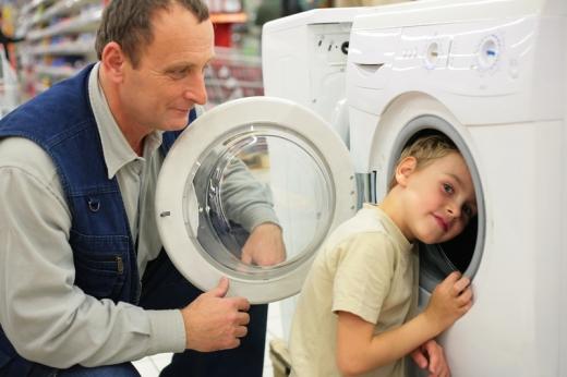 Egy áruházban a kisfiú feje a mosógépben, apuka meg nézi mögüle.