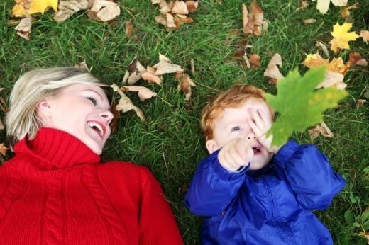 Nő és gyereke fekszik háton a fűben, a kisfiú kezében egy falevél.