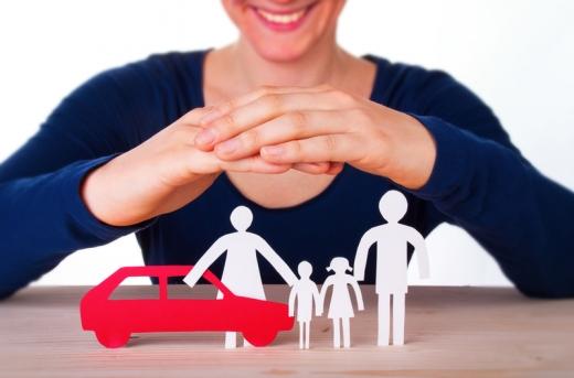 Az asztalon papírból egy piros autó és egy négytagú család, ez felett pedig egy nő két keze, mintha felülről védené őket.