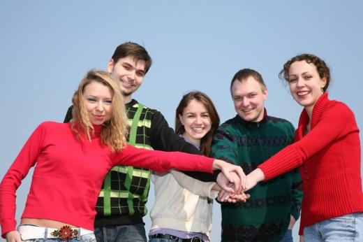 Három nő és két férfi felénk néz és a kezüket egymásra rakják.