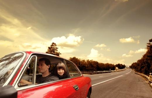Az úton megy egy piros autó, amiben ül egy férfi és a gyereke.