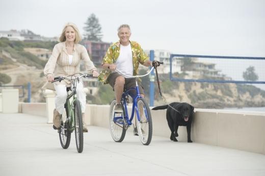 Egy középkorú pár biciklizik és a férfi közben pórázon vezeti a kutyáját.
