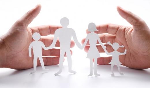 Két kéz között papírból kivágott házaspár két gyerekkel.