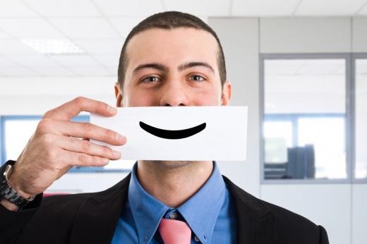 Egy öltönyös férfi egy papírlapot tart a szája előtt amin egy mosolyjel van.