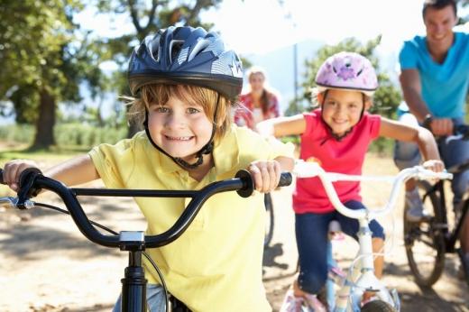 Két kisgyerek egymás mögött biciklizik, mögött a szüleik.