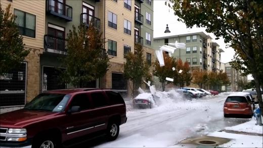 Egy utcán egy autóra rázúdul a jég.