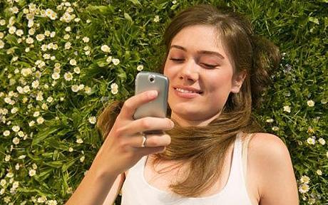 Egy lány fekszik a fűben és a telefonját nézi.