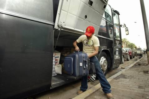 Egy férfi piros sapkában, csomagot vesz le a busz csomagteréből.