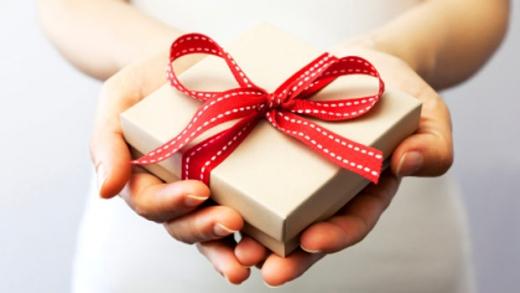 Egy kézben egy doboz piros masnival átkötve.