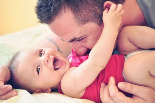 Apuka játszik a kisbabájával.
