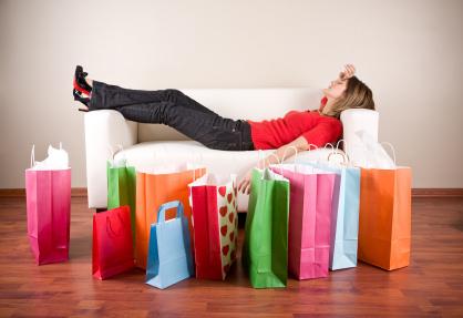Egy nő fáradtan fekszik a kanapén előtte teli papírzacskókkal.