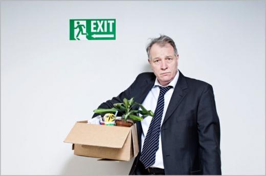 Egy öltönyös férfi, kezében egy doboz amiben a munkahelyi dolgai vannak, felette egy EXIT felírat.