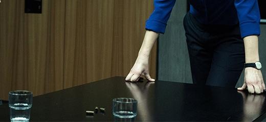 Egy férfi egy fekete asztalra támaszkodik.