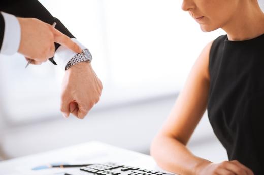 A főnök az órájára mutat női alkalmazottjának.