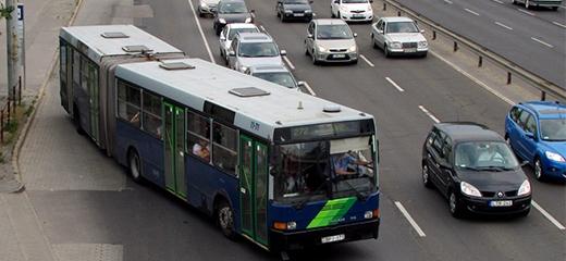 Többsávos úton egy kék busz sávot vált.
