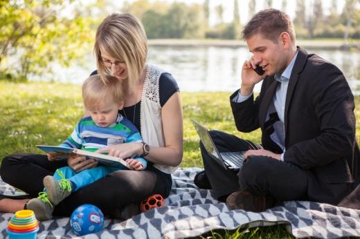Egy pár a kisgyerekével piknikezik, ami közben a férfi laptoppal és telefonnal dolgozik.