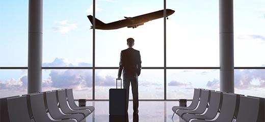 Egy reptér várójában egy férfi egyedül áll az ablaknál ahol egy repülő száll fel.