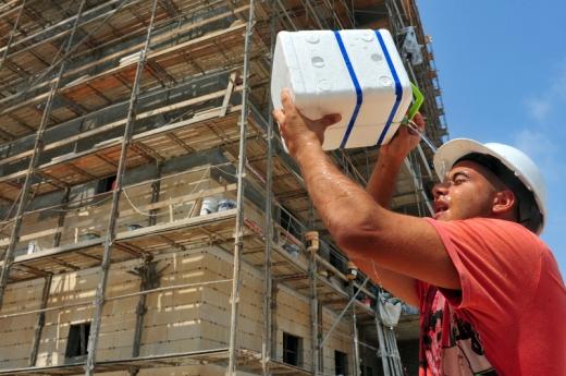 Egy építkezésen egy építőmunkás vizet önt magára.