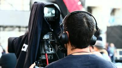 Egy operatőr kamerával hátulról látszik.