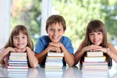 Három gyerek egy asztalon könyvkupacra támaszkodik a fejével.