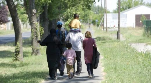 Egy migráns család sétál velünk háttal egy utcán.