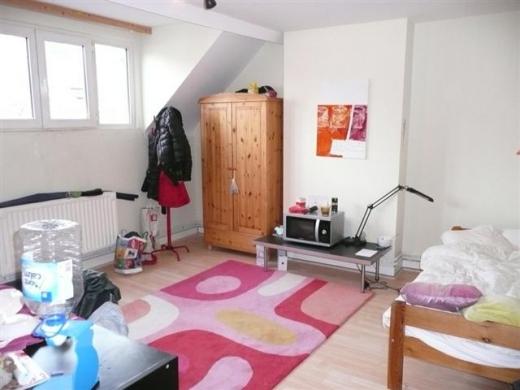 Egy szoba, amiben ágy, szekrény, fogas, szőnyeg van.