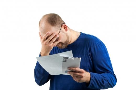 Egy férfi a fejét fogva néz egy levelet.