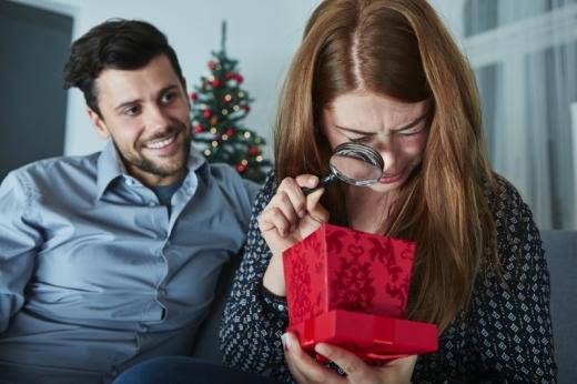 Egy pár van a karácsonyfa előtt, ahol a nő nagyítóval néz bele a karácsonyi dobozába.