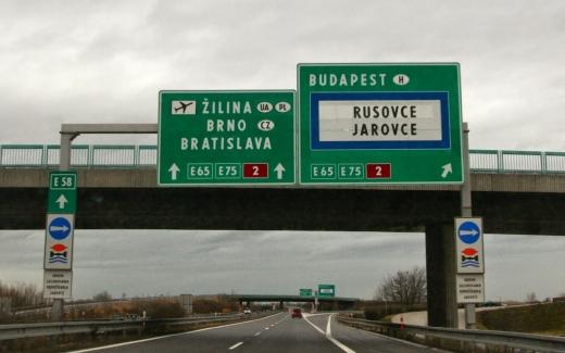 Egy autópálya kép, ahol egy nagy zöld tábla mutatja merre van Budapest és Bratislava.