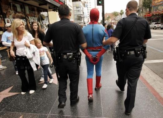 Egy pókember jelmezes férfit megbilincselve kísér két rendőr az utcán.