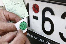 Egy kéz környezetvédelmi zöld matricát ragaszt a rendszám táblára.