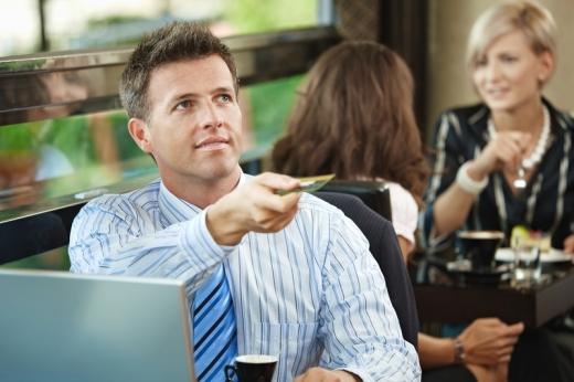 Egy férfi laptopnál ülve bankkártyát kínál felénk.