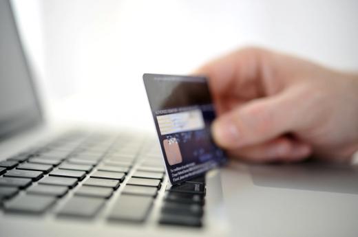 Egy kéz bankkártyát tart egy laptop billentyűzete felett.