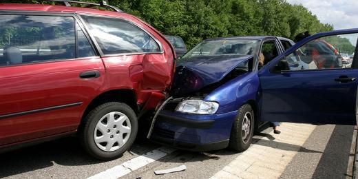 Egy kék autó belement egy piros autóba.