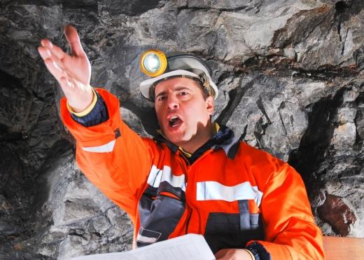 Egy barlangban a barlangász előre mutat és kiabál.
