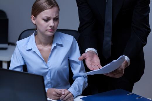 Egy férfi szemrehányóan egy nő elé tart egy papírt.