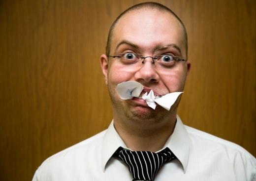 Egy szemüvege férfi szája tele van tömve papírral.