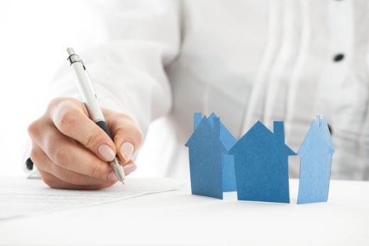Egy kézi aláír egy papírt egy asztalon, amin kék papírház van.