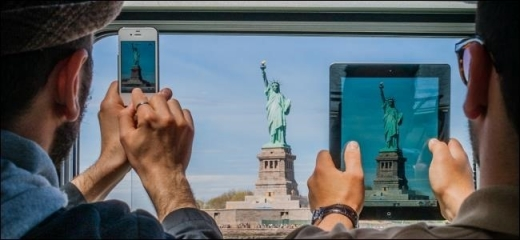 Egy férfi táblagéppel, egy másik férfi telefonnal fényképezi a szabadság szobrot.