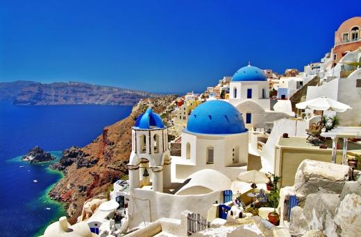 Egy görög tengerparti domb fehér falú, kék tetejű házakkal.