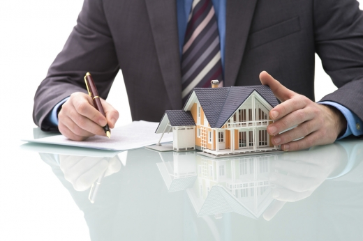 Egy férfi egy asztalon egyik kezével háza fog, a másikkal aláír.
