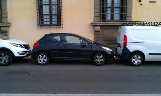 Egy fekete autó, egy ház előtt parkol két fehér autó között.