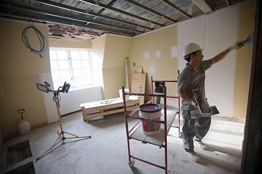 Egy festő egy üres szobában a falat javítja.