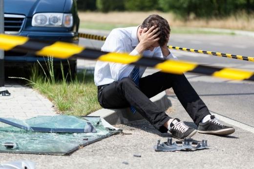 Egy férfi az út mellett ül egy karambol után és a fejét fogja.