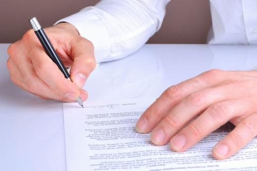 Egy férfi keze aláír egy szerződést.